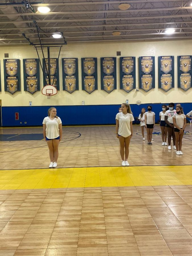 Both captains, Lainey Haralson and Kennadi Brown teaching their teammates their routine.